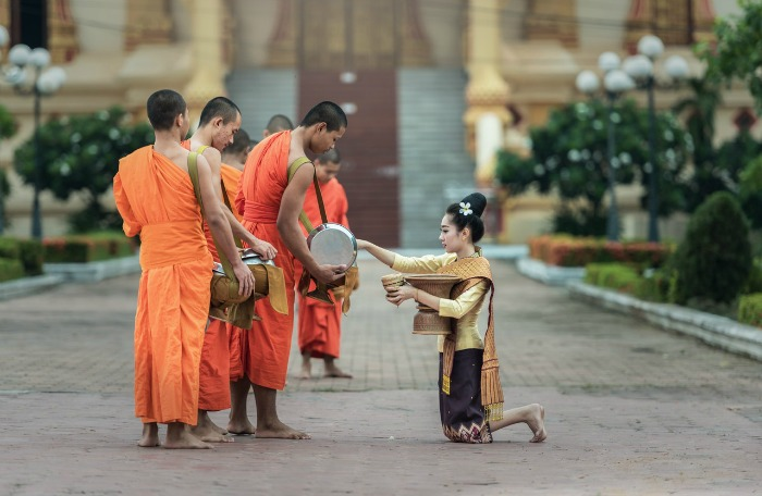 A woman gives to Theravada Buddhist monks