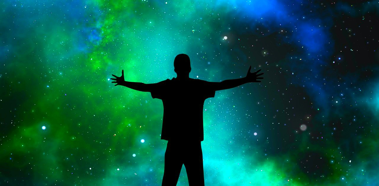 Silhouette of man in front of Universe