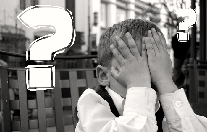 Boy Covering his face with question marks in the air behind him
