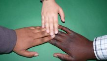 three hands of various races touching