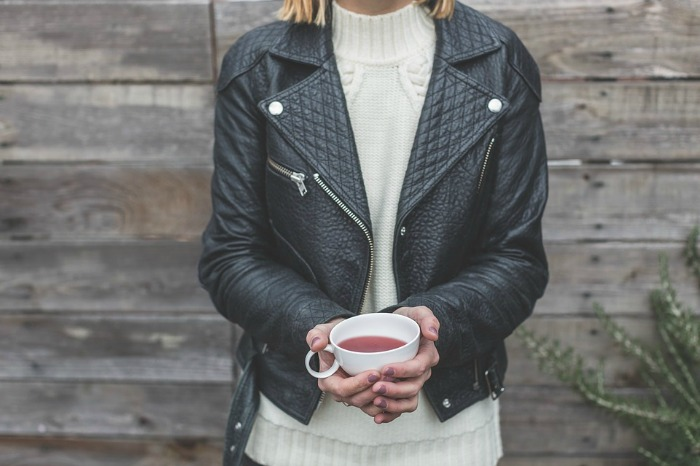 A Leather Jacketed Woman Holding tea in Front of wooden wall