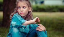 A young girl sits beneath a tree on the grass wearing jeans and a jean jacket with a sad/forlorn look on her face