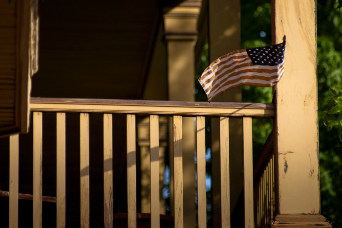 House porch flanked by American Flag