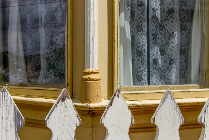 Partial view of picket fence and corner windows covered in lace curtains
