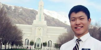 An LDS missionary of Asian decent is seen posing in front of an LDS temple with mountains in the background