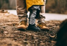 A close up shot of the feet of an adult and a child on the shores of a river