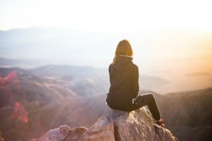 A young woman sits atop of a mountain overlooking the breathtaking view of mountains, a lake, and the sun
