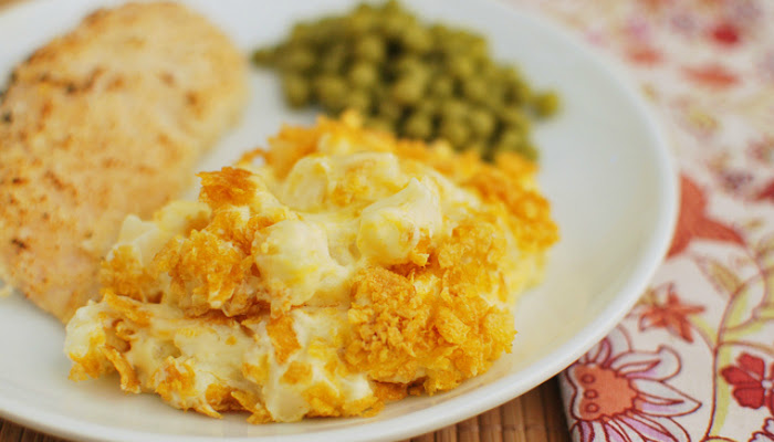 A plate with funeral potatoes, peas and grilled chicken is shown with the potatoes in focus and the rest blurred in the background.