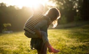 A young girl is giving a little boy a piggyback ride in a grassy area with the sun's glare peaking above their silhouetted heads.