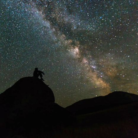 man outdoors gazing at the milky way