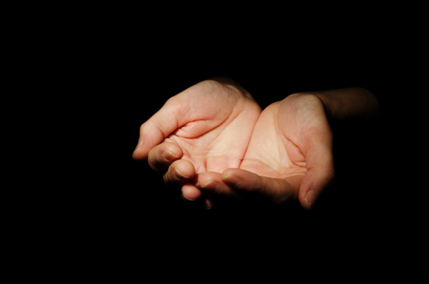 Person offering compassionate, outstretched hands