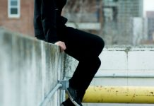 A teenager (gender unclear) dressed all in black is sitting atop of a wall, presumably on a roof top. Their head is cut off and we only see their legs and pipes and outlets on the wall