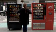 A woman stands between two vending machines, one black and on red, and appears to be attempting to choose between them