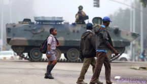 An armored tank is seen blocking part of an intersection as citizens continue about their daily lives and walk past