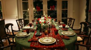 An elaborate Christmas table is set in a dining room with beautiful goblets and dishes