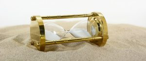 A golden hourglass lays on its side as it sits atop a mountain of sand