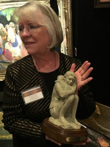 "Annette Whitaker Everett holds her sculptural piece, ""Rest and Be Thankful,"" depicting a mother and child, at the Inspirational Art Association's 8th Annual Joseph Smith Memorial Building Christmas Art Showcase."