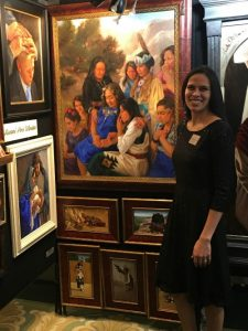 Artist Kwani Povi Winder poses with her art display at the Inspirational Art Association's 8th Annual Joseph Smith Memorial Building Christmas Art Showcase.