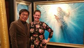 "Katie Garner and Yongsung Kim pose in front of Kim's large-scale painting entitles ""The Hand of God."""