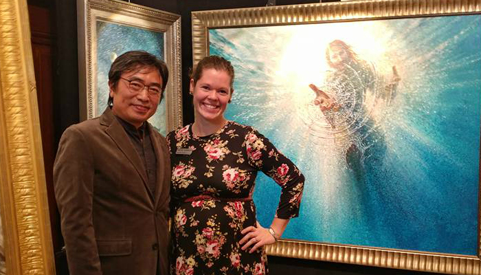 Katie Garner and Yongsung Kim pose in front of Kim's large-scale painting entitles