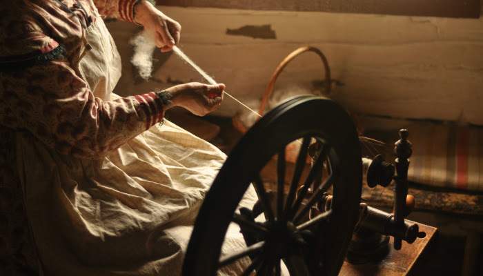 A pioneer woman spins thread using an old fashioned machine