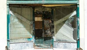 A derelict storefront with falling, dirty blind in the two windows surrounding the dirty, board/paper covered door