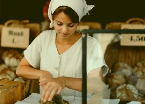 A young girl wearing simple clothing like a white bonnet/bandanna is cutting what appears to be bread with a cleaver as she works at a shop