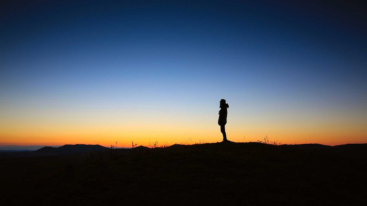 Silhouette of person with sunset in background.