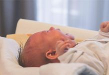 Baby cries on hospital bed