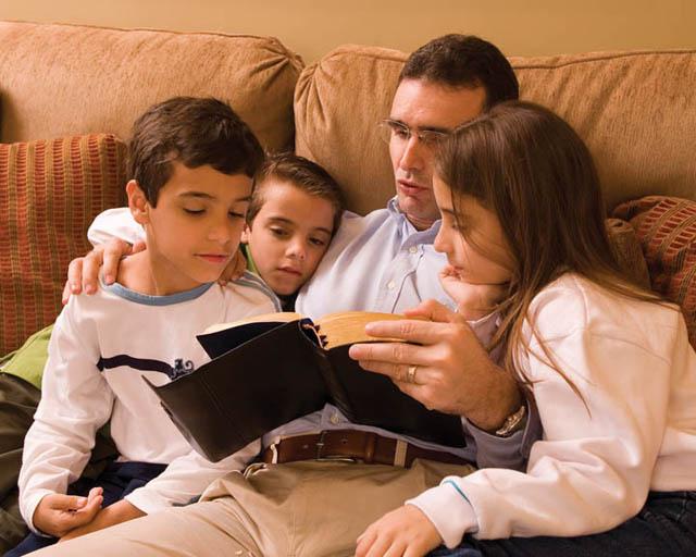 Mormon father reading scriptures to children