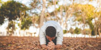 man praying on ground covered with leaves