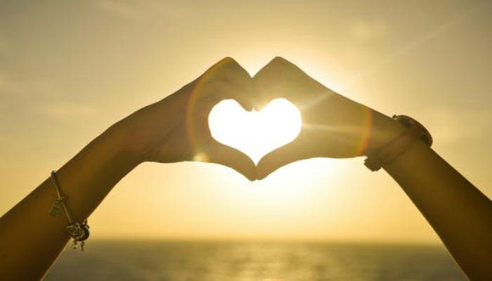 sunset hands into heart