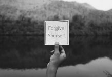 "Hand holding card in nature with ""Forgive Yourself"" text on it."