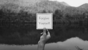"""Hand holding card in nature with """"Forgive Yourself"""" text on it."""