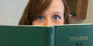 Girl's face behind LDS hymnal