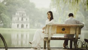 man and woman sitting on bench turned away from each other
