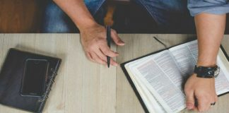 Man's hand with scriptures, cell phone, and journal on a table