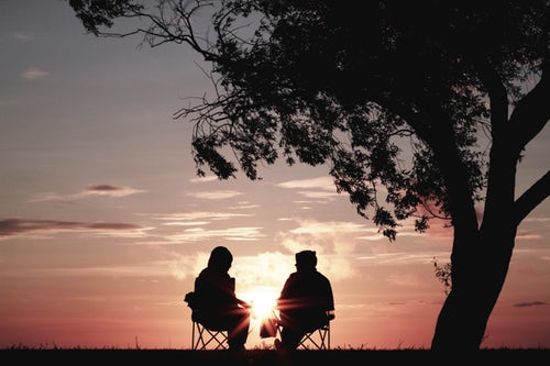 Two people sitting in lawn chairs with a pink sunset as a backdrop