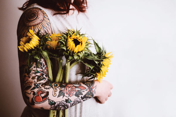 tattooed arm holding flowers