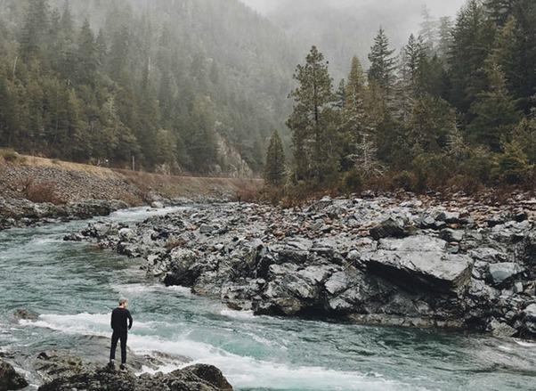 man standing river wild