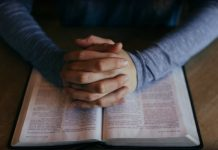Man folding hands over scriptures