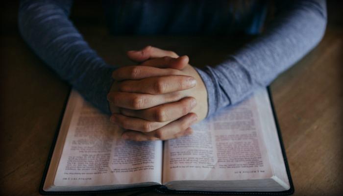 Hombre doblando las manos sobre las escrituras
