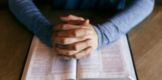 Hands folded over an open Bible.
