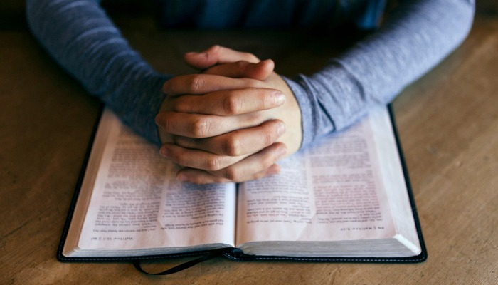 Hands folded over an open Bible.
