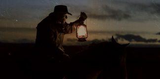 Cowboy riding a horse, holding a lantern.