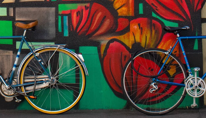Bikes in front of a wall of graffiti.