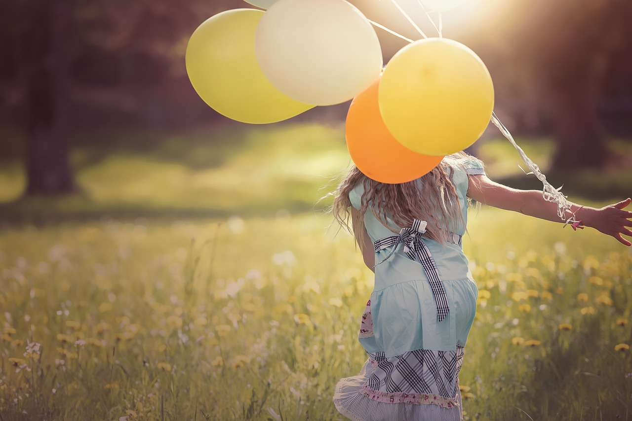 Girl playing with balloons.
