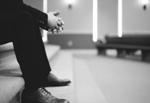 B&W legs of man praying alone in church