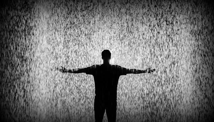 Silhouette of man standing in rain.