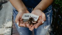 """Hands holding coins and paper saying """"Make a change"""""""